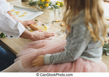 Young family making cookies at home. food, family, christmas, hapiness and people concept - smiling family making a gingerbread cookie