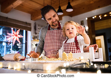 Young family making cookies at home. - Man and toddler boy...