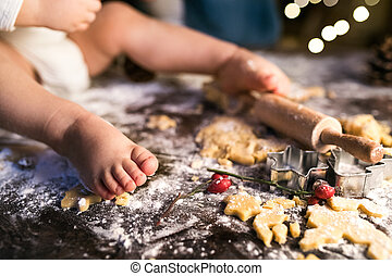 Young family making gingerbread cookies at home....