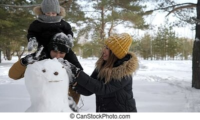 Young family, mom, son and dad are building a snowman in winter city park.