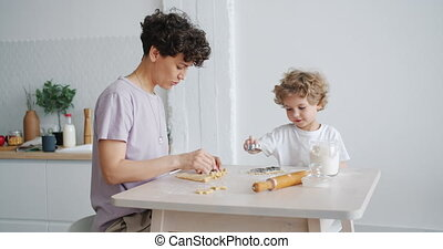 Young family mother and child making cookies at kitchen...
