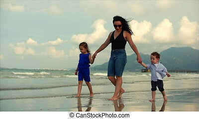 Young family, mother and children are walking along the coast. Happy family walking on sea coast.