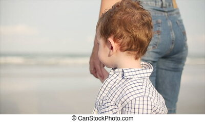Young family, mother and son are watching the waves of the ocean. A happy family walks along the seashore.