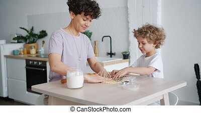 Young family mother and son making home-made cookies at...