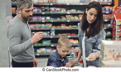 Young family mother, father and child and choosing sweets in food store, taking products and looking at them then putting in trolley. Shelves with tasty food are visible.