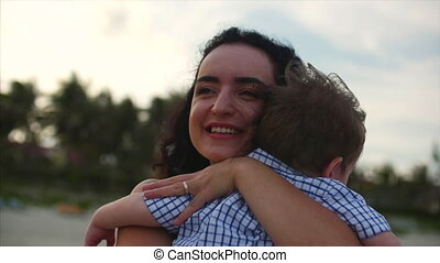 Young family, mother hugging her son on the coast. Happy family, along the seacoast.