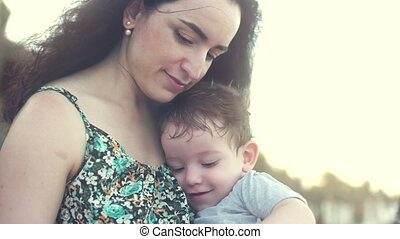 Young family, mother with son in her arms. Happy son touches the hands mother smiles.