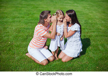 Young family of three sitting on the grass and have fun