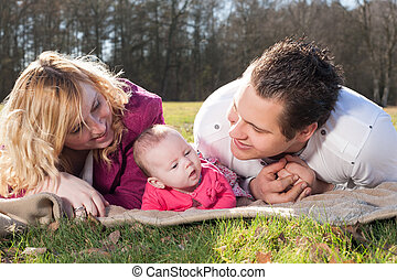 Young family on a blanket in the grass