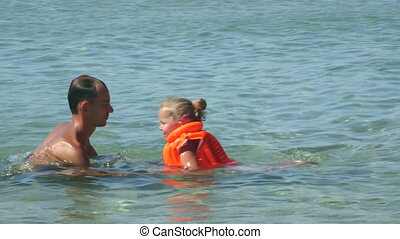 Young family on beach vacation have fun in water teaching daughter how to swim