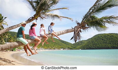 Young family on beach vacation on palmtree