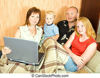 family on sofa with laptop