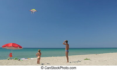 Young family on summer beach vacation having fun together flying kite in the sky