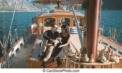 Young family on yacht sailing on lake in summer outdoors
