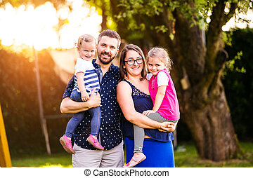 Young family outside in sunny summer park, green nature