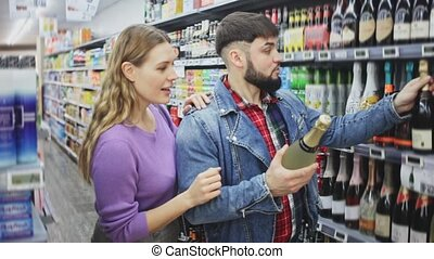 Portrait of young man and woman choosing bottle of cava in grocery shop