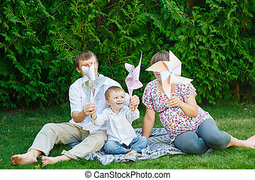 young family playing on a picnic in the summer park