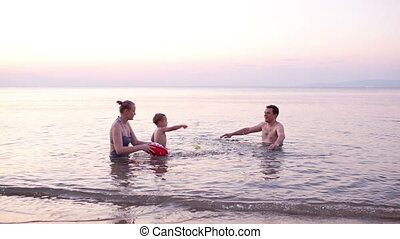 Young family playing red toy boat at sunset