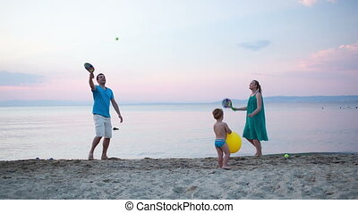 Young family playing tennis at the seaside