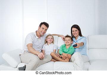 young family posing on sofa