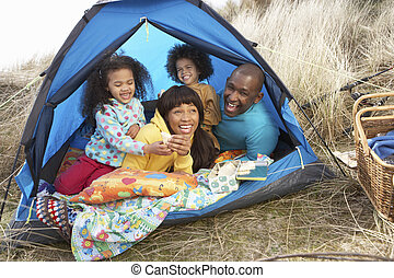 Young Family Relaxing Inside Tent On Camping Holiday