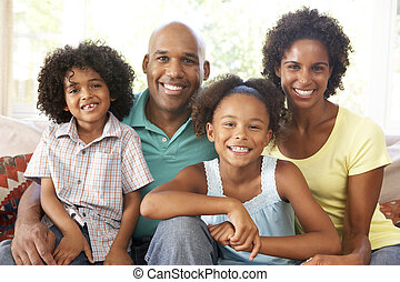 Young Family Relaxing On Sofa At Home