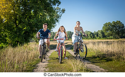 Young family riding on bicycles at meadow. Concept of family sport