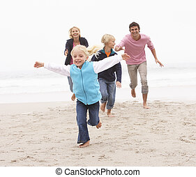 Young Family Running Along Winter Beach