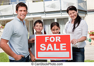 Young family selling their home with sale sign