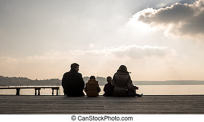Young family sitting on a wooden deck at sunset