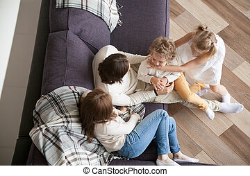 Young family sitting on couch in living room at home