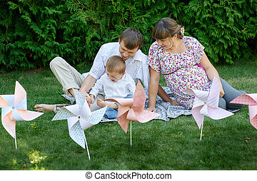 Young family sitting on the grass in a park with toys