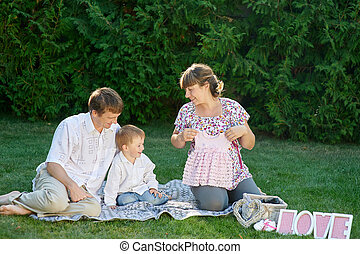 Young family sitting on the grass in a summer park with letters love