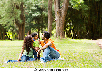 young family sitting outdoors