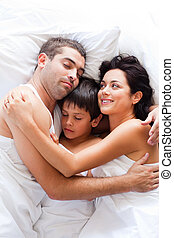 Young family sleeping in bed
