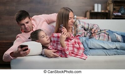 Young family spending time with electronic devices