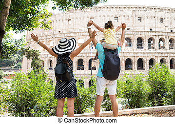 Young Family Standing In Front Of Colosseum