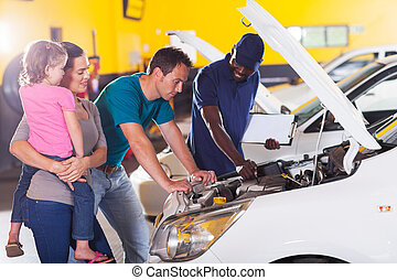 young family taking their car for repair in garage