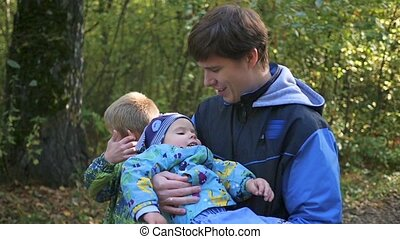 Young family walking in the park, father carrying son in his arms
