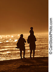 young family walking on beach