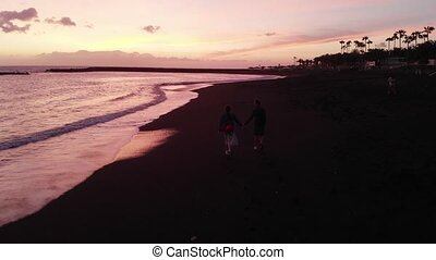 Young family walks along the black beach on the ocean at sunset, view from the drone. Tenerife, Spain.