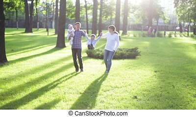 young family walks in the summer park on the grass