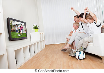 Young family watching football
