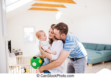 Young family with a baby boy at home, standing.