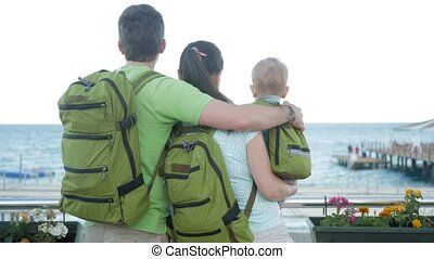 Young family with a baby looking at the sea and hugging. Everyone has backpacks on their backs. Beach and people