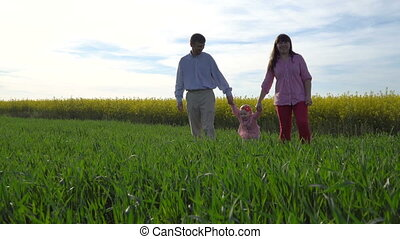 young family with a daughter walks through the spring green meadow