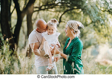 Young family with a small daughter in sunny summer nature.
