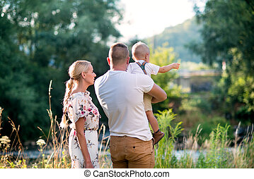 Young family with a small toddler boy in sunny summer nature. Rear view.