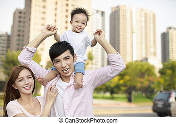 Young family with baby having fun in city park
