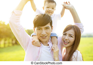 Young family with baby having fun in nature